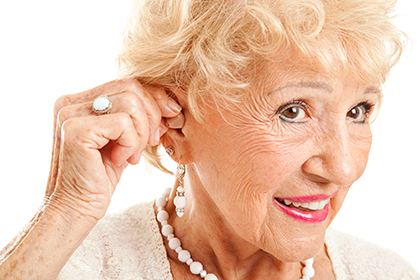 Photo of retiree putting in a hearing aid